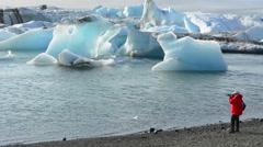 Iceland Jokulsarlon glaciers and icebergs on lake lagoon with photographers on Stock Footage