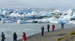Iceland Jokulsarlon glaciers and icebergs on lake lagoon with photographers Stock Footage