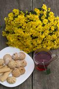 Glass of tea, bouquet of yellow flowers and plate with cookies Stock Photos