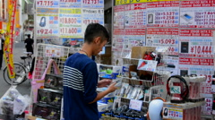 Tokyo Japan modern high tech area called Akihabara area man looking to buy Stock Footage