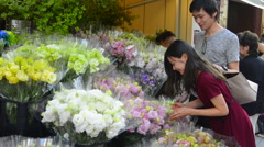 Tokyo Japan Ginza Shopping street couple buying beautiful flowers from shop on Stock Footage