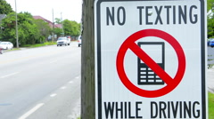 NO TEXTING WHILE DRIVING sign dangerous practice Stock Footage