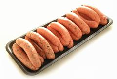 raw uncooked sausages on retail tray - stock photo