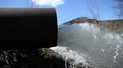 Stock Video Footage of A black storm drain pipe with storm water runoff