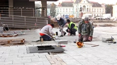 Workers stack paving slabs on city streets Stock Footage