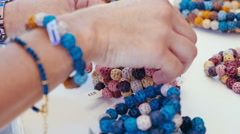 A girl buy handcrafted bracelets Stock Footage