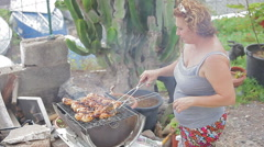 A woman roasting chicken thighs Stock Footage