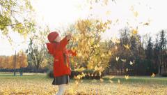 Happy child girl throws up autumn leaves in the park and laughing at camera - stock footage
