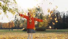 Happy child girl 7 years old throws up autumn leaves in the park and smiling - stock footage