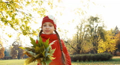 Portrait happy girl 7 years old holding and hugging a bouquet of autumn leave Stock Footage