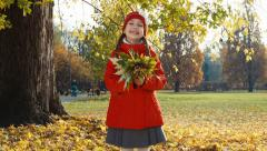 Portrait happy child girl holding a bouquet of autumn leaves - stock footage