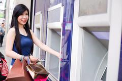 Young japanese woman withdrawing cash from an atm while out shopping Stock Photos