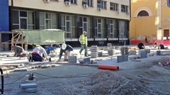 Workers stack paving slabs on city streets - stock footage