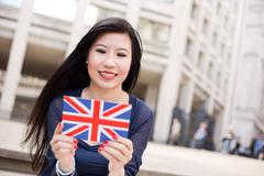 Japanese woman reading a post card with the union jack Stock Photos