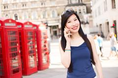 Japanese woman in London using her mobile phone - stock photo