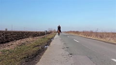 Man is riding a horse on rural landscape, road of asphalt. Stock Footage