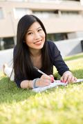 Japanese student lying on the grass with a textbook - stock photo