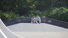 4K Friends at skate park, looking at computer & doing parkour jumps Stock Footage