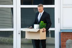 Unhappy Young Businessman Carrying His Belongings In Box After Being Fired - stock photo