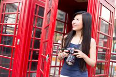 Japanese tourist in London holding a camera - stock photo