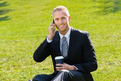 Young Smiling Man Holding Disposal Cup In Hand Talking On Cellphone Stock Photos