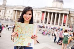 japanese woman in Trafalgar square reading a map - stock photo