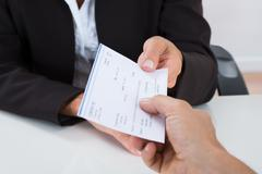 Close-up Of Businessperson Hands Giving Cheque To Other Person At Desk Stock Photos