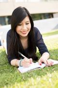 Japanese student lying on the grass writing - stock photo