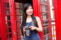 japanese tourist in london holding her camera - stock photo