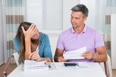 Worried Couple Looking At Unpaid Bills At Home - stock photo