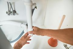Cropped image of plumber working on pipes under kitchen sink Stock Photos