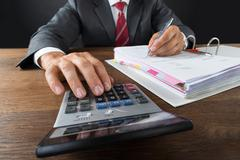 Midsection of accountant checking invoice with calculator at desk against gra Stock Photos