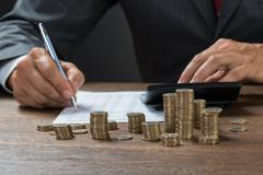 Cropped image of accountant calculating profit with coins on desk Stock Photos