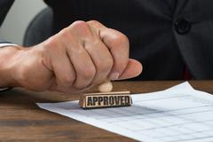 Cropped image of businessman stamping document marked with approved at desk Stock Photos