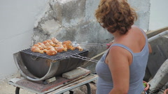 A woman roasting chicken thighs at barbecue Stock Footage
