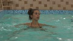 Pregnant woman takes break in aquafit class Stock Footage
