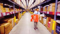 Blurred Image Inside A Modern Warehouse.With Unidentical Person Holding The G - stock photo