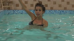 Pregnant woman raises hands out of water in aquafit class Stock Footage