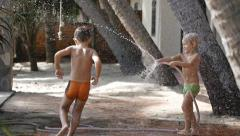 Cute adorable boys spraying with a garden hose in the back yard. Slow motion - stock footage
