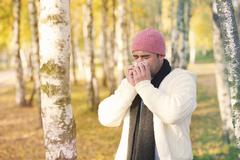 man in park blowing his nose - stock photo