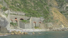 Tourists taking a bath near a stone wall in Cinque Terre Stock Footage