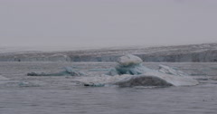 Cruising Past Blue Iceberg with Ice Sheet in Background Stock Footage