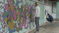 Two guys painting colorful graffiti on wall with sprays, shallow depth of field. Stock Footage