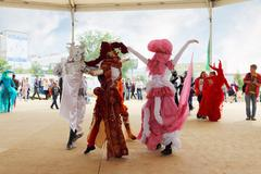 People in costume dancing on street theaters show at open air - stock photo