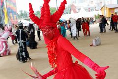 Dancer in red costume poses on street theaters show Stock Photos
