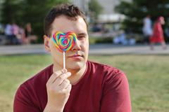 Stock Photo of Handsome man hides his eye behind lollipop outdoor at summer sunny day