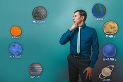 Man holds his chin thinking planets of the solar system astronom Stock Photos