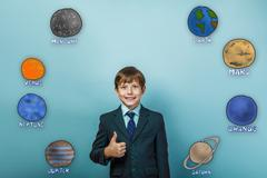Teen boy businessman showing a sign and the smiles of the planet - stock photo