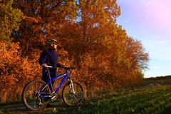 Young adult cyclist riding mountain bike in the countryside Stock Photos