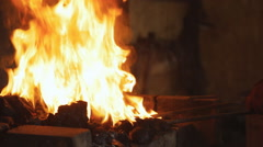 Operating smithy fire flame tips with sparks on dark background, with the Stock Footage